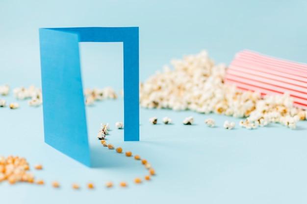 Sementes de milho passando por porta de papel azul, transformando em pipoca em pano de fundo azul Foto gratuita