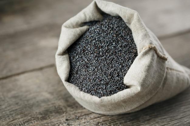 Sementes de papoila em um saco de serapilheira. as sementes saborosas e úteis, ricas em proteínas e óleos. Foto Premium