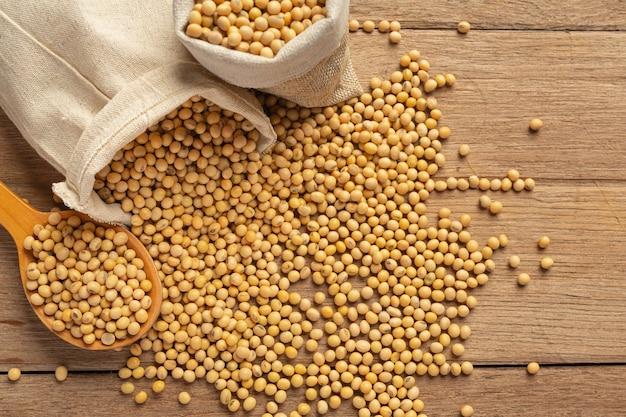 Sementes de soja em sacos de piso de madeira e cânhamo conceito de nutrição alimentar. Foto gratuita