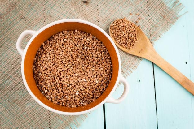 Sêmola de trigo sarraceno em uma tigela e uma colher de pau Foto Premium