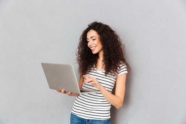 Senhora adorável com cabelo encaracolado e-mail com sua amiga usando laptop prata sendo isolado sobre parede cinza Foto gratuita