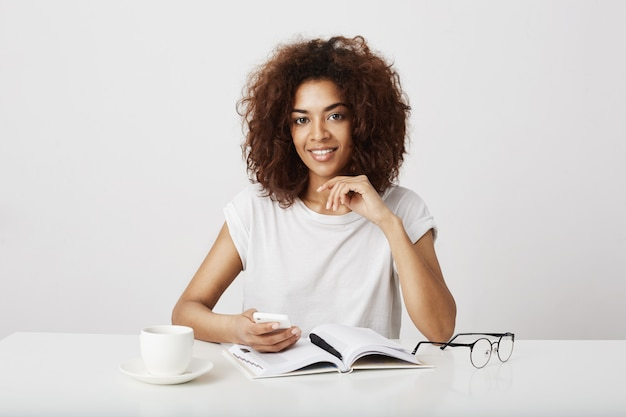Senhora africana do negócio que sorri guardando o telefone que senta-se no local de trabalho sobre a parede branca. copie o espaço. Foto gratuita