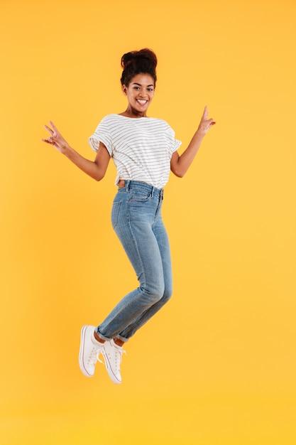 Senhora alegre africana engraçada pulando e sorrindo isolado Foto gratuita
