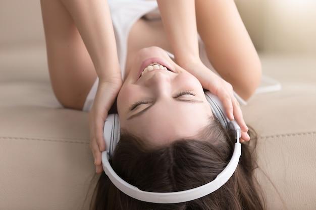 Senhora alegre, apreciando a música popular em fones de ouvido Foto gratuita