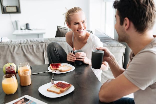 Senhora alegre atraente olhando para o homem enquanto eles tomam café da manhã Foto gratuita