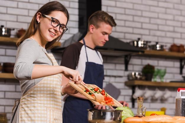Senhora alegre cozinhar salada perto de namorado Foto gratuita