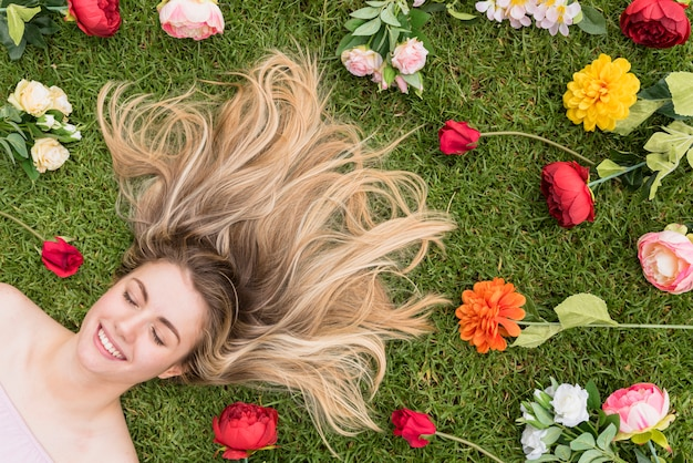 Senhora alegre deitado na grama entre flores Foto gratuita