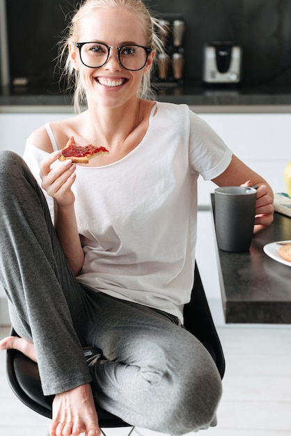Senhora alegre em copos sentado com pão e xícara de chá na cozinha Foto gratuita