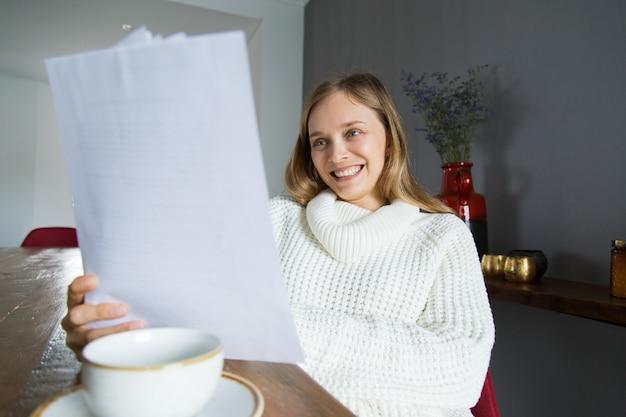 Senhora alegre na camisola branca, examinando os papéis em casa Foto gratuita