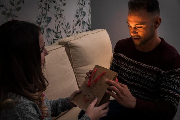 Senhora apresentando pacote de presente para o cara no sofá Foto gratuita
