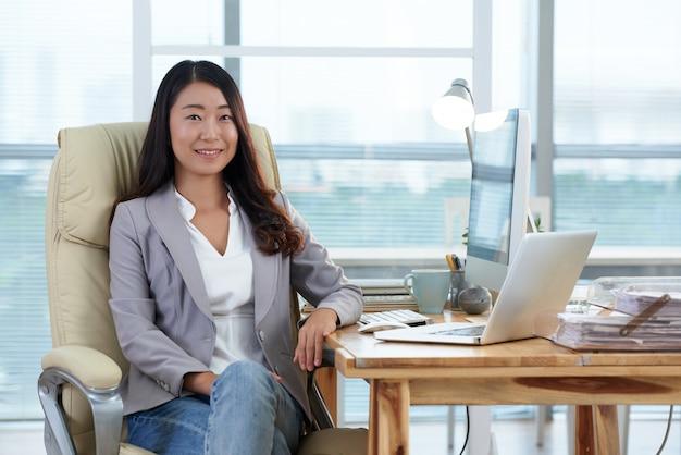 Senhora asiática elegantemente vestida, sentado no escritório com computador e laptop e sorrindo Foto gratuita