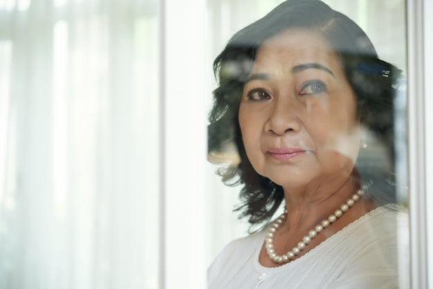 Senhora asiática idosa, olhando para fora através do vidro da janela Foto gratuita