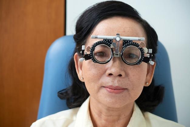 Senhora asiática madura, usando armação de lente experimental durante o exame da visão Foto gratuita