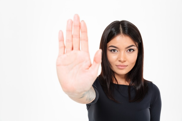 Senhora asiática séria concentrada nova que mostra o gesto da parada Foto gratuita