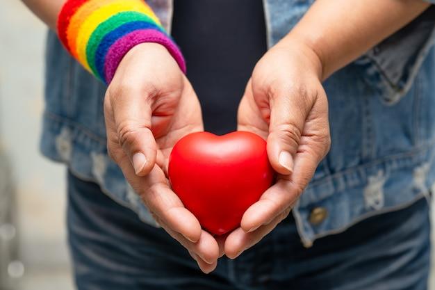 Senhora asiática usando pulseiras de arco-íris e segurando um coração vermelho, símbolo do mês do orgulho lgbt. Foto Premium