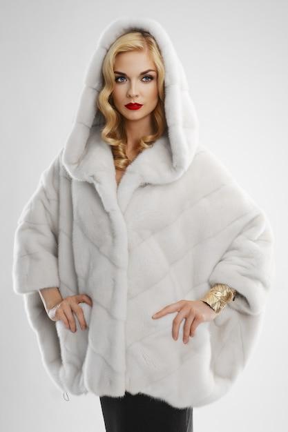 Senhora atraente com casaco de pele branca com capuz na cabeça Foto Premium