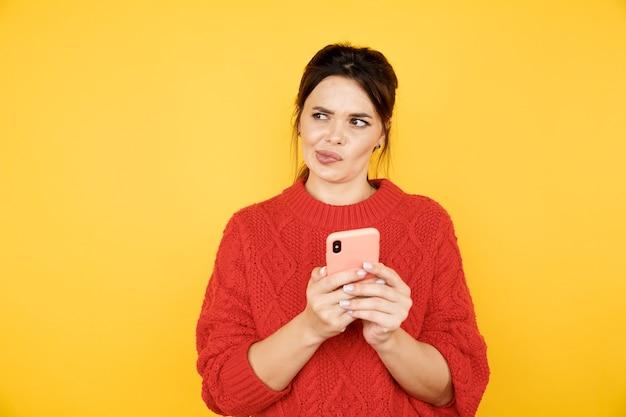 Senhora bonita em pose de pensamento com o telefone nas mãos isolado sobre o fundo amarelo. Foto Premium