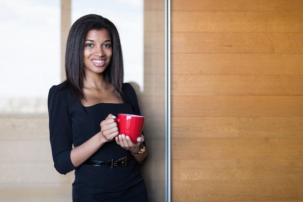 Senhora bonita, jovem de negócios na suite forte preta segurar copo vermelho Foto Premium