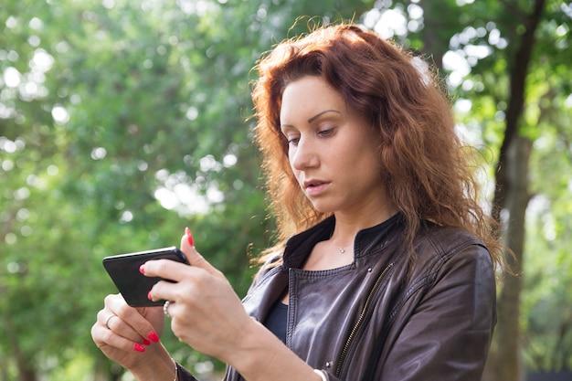 Senhora bonita séria navegando em smartphone no parque da cidade Foto gratuita