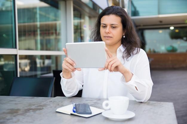 Senhora bonita séria que lê a notícia na tabuleta no café da rua Foto gratuita