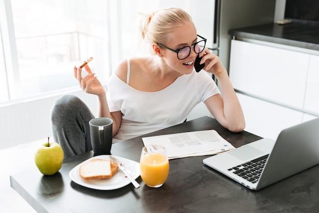 Senhora bonita trabalhando com laptop e falando no smartphone e tomando café da manhã Foto gratuita