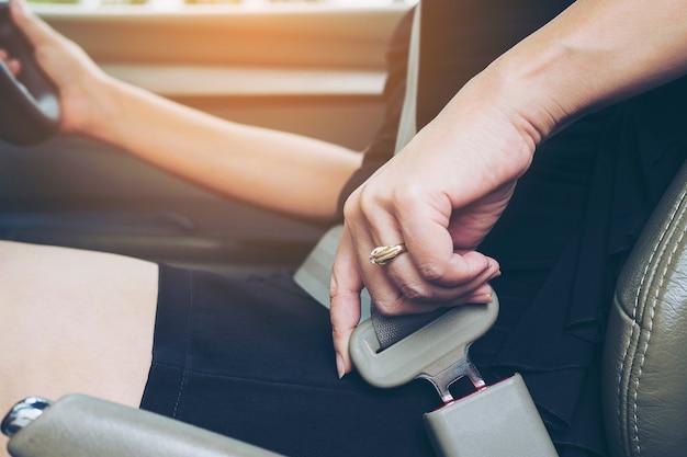 Senhora, colocando o cinto de segurança antes de dirigir, fechar na fivela do cinto, conceito de unidade segura Foto gratuita