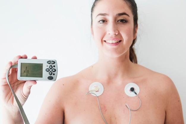 Senhora, com, eletrodos, segurando, monitor, com, cardiograma Foto gratuita