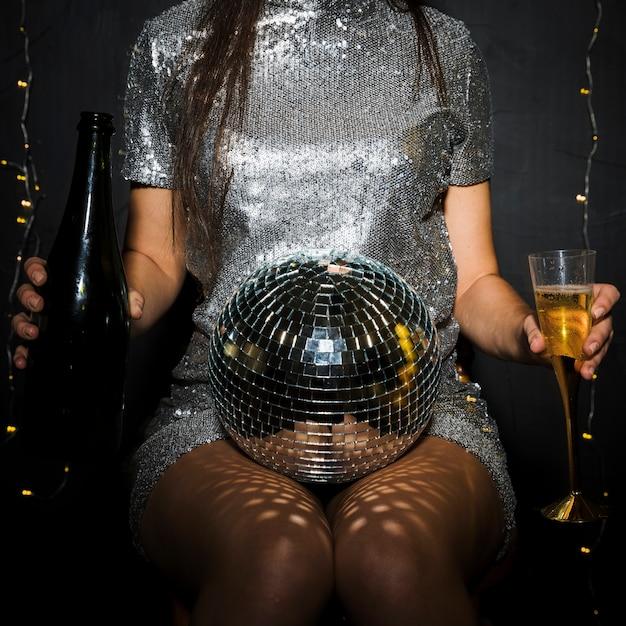 Senhora com garrafa de champanhe, vidro e bola de discoteca Foto gratuita