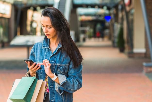 Senhora com sacos de compras usando smartphone no shopping Foto gratuita