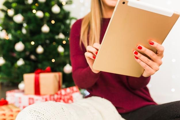 Senhora com tablet perto de caixas de presente e árvore de natal Foto gratuita