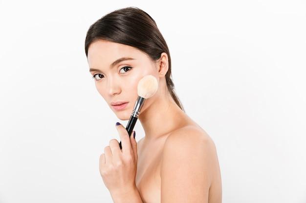 Senhora confiante segurando o pincel de maquiagem e isolado Foto Premium