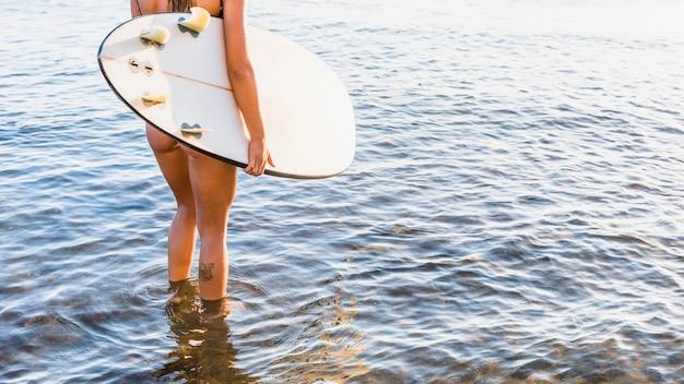 Senhora da colheita com a prancha no mar Foto gratuita