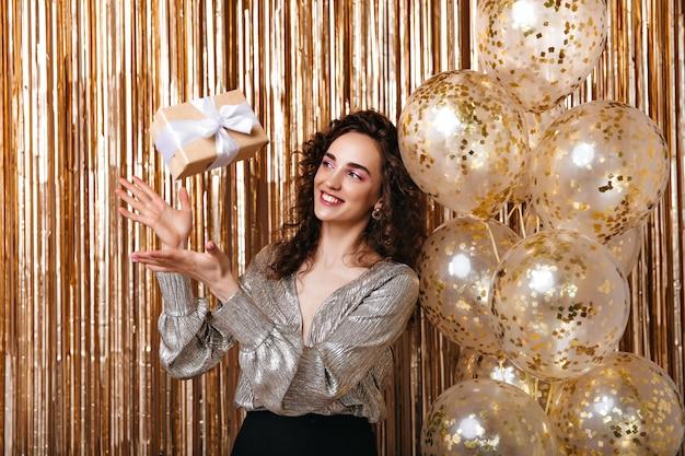 Senhora de blusa prateada jogando uma caixa de presente sobre fundo dourado Foto gratuita