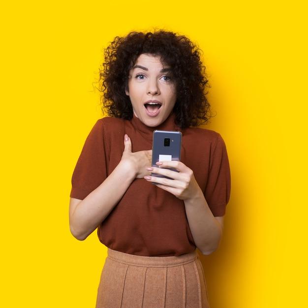 Senhora de cabelos cacheados apontando para si mesma, segurando um celular e posando em uma parede amarela com espaço em branco Foto Premium