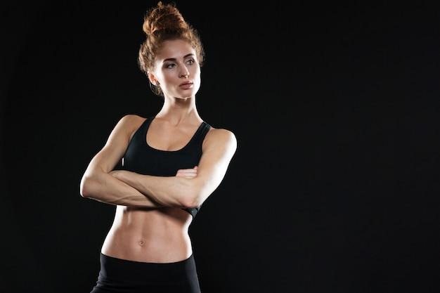 Senhora de esportes jovem sério posando com os braços cruzados Foto gratuita