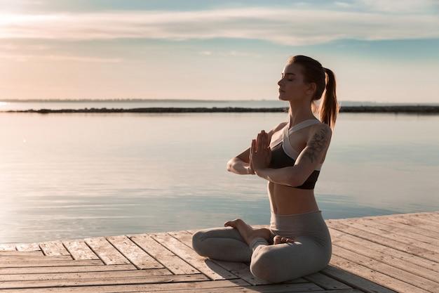 Senhora de esportes na praia fazer meditar exercícios. Foto gratuita
