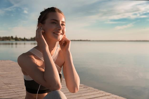 Senhora de esportes sorridente na praia ouvindo música com fones de ouvido Foto gratuita