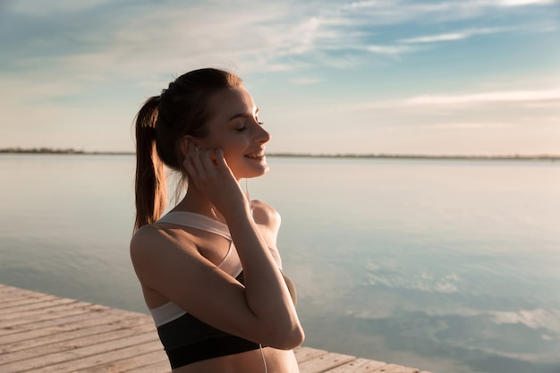 Senhora de esportes sorridente na praia ouvindo música Foto gratuita