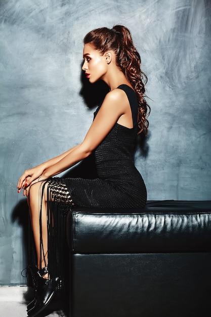 Senhora de modelo sexy mulher bonita com lábios vermelhos em vestido preto elegante, sentado no sofá perto da parede cinza Foto gratuita