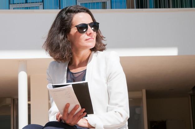 Senhora de negócios pensativo lendo suas anotações Foto gratuita