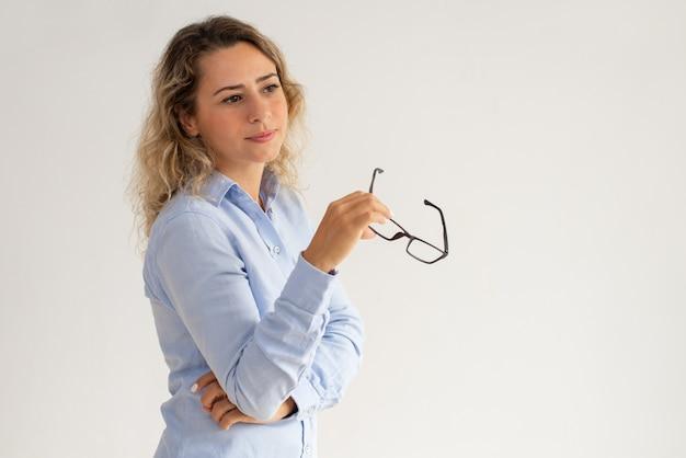 Senhora de negócios pensativo sonhador segurando óculos e desviar o olhar Foto gratuita