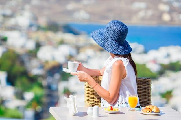 Senhora elegante bonita tomando café da manhã no café ao ar livre com uma vista incrível da cidade de mykonos. mulher tomando café quente no terraço do hotel de luxo com vista para o mar no restaurante do resort. Foto Premium