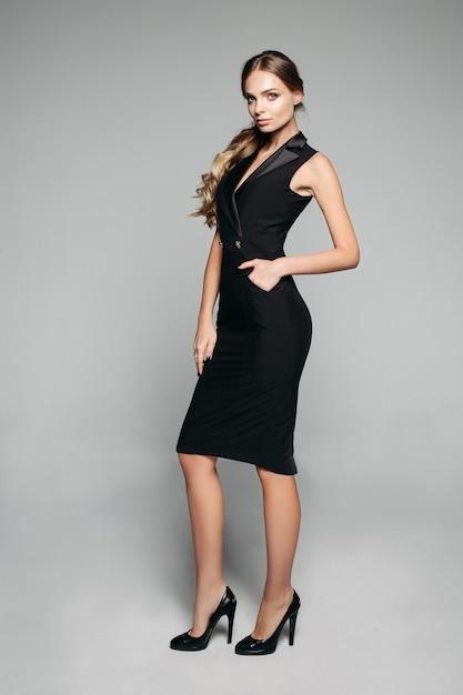 Senhora elegante no escritório preto vestido e salto alto. Foto Premium