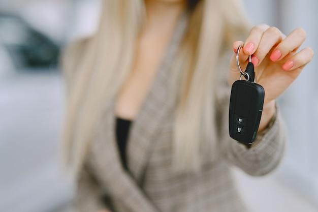 Senhora em um salão de automóveis. mulher comprando o carro. mulher elegante em um terno marrom. Foto gratuita