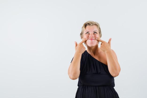 Senhora encantadora fazendo sorriso falso na vista frontal de blusa preta. Foto gratuita