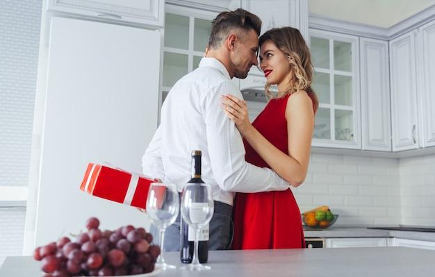 Senhora encantadora sorridente, abraçando o homem enquanto ele esconde o presente para ela Foto gratuita