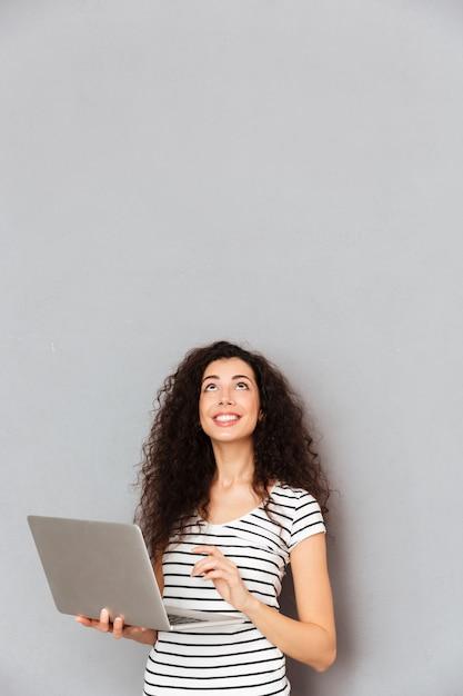 Senhora feliz com cabelos cacheados, escrever a mensagem ou se comunicar na internet usando laptop prata sendo isolado sobre parede cinza Foto gratuita