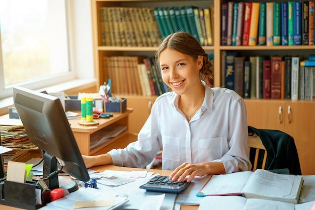 Senhora feliz nova do negócio na camisa branca que senta-se na tabela com computador e papéis que trabalham o ambiente. Foto Premium