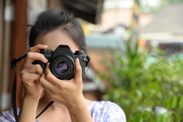 Senhora fotógrafo em vestido vintage segurando a câmera de filme retrô na mão Foto Premium