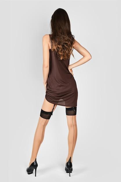 Senhora irreconhecível, levantando o vestido e mostrando meias e liga Foto Premium